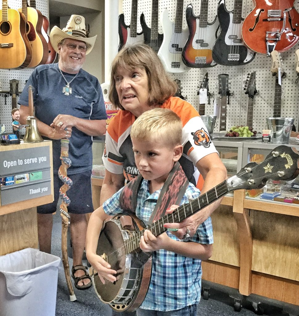 Young man getting his first experience as a banjo picker at the August 31, 2019 Grand Opening of Vernon McIntyre's Famous Old Time Music Company